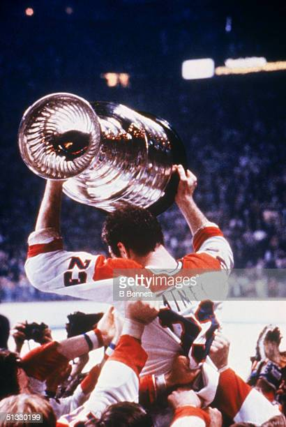 Bob Gainey of the Montreal Canadiens hoist the Stanley Cup as he is being carried by his teammates after defeating the New York Ranges in the 1979...