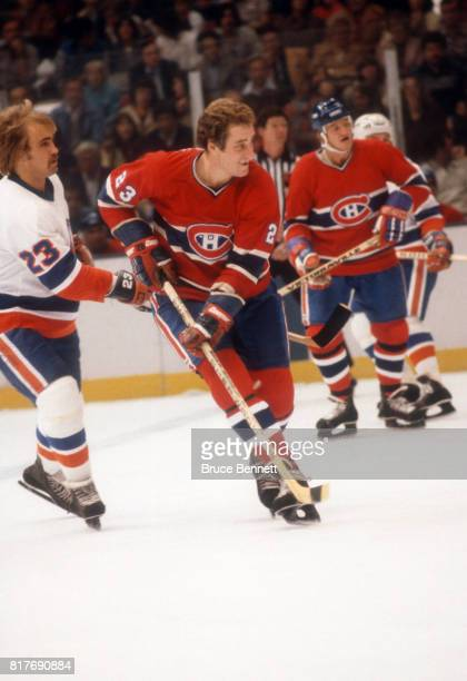 Bob Gainey of the Montreal Canadiens skates on the ice as he is defended by Bob Nystrom of the New York Islanders on October 17 1978 at the Nassau...