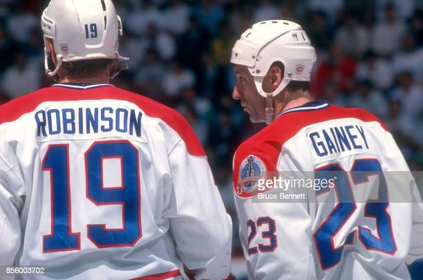 Bob Gainey of the Montreal Canadiens talks with his teammate Larry Robinson during a 1989 Stanley Cup Finals game against the Calgary Flames circa...