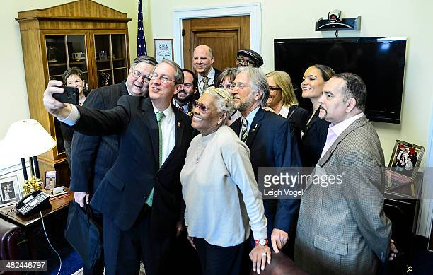 Bob Goodlatte takes a photo during a meeting with Dionne Warwick Neil PortnowBooker T Jones and other members of the Recording Academy during...