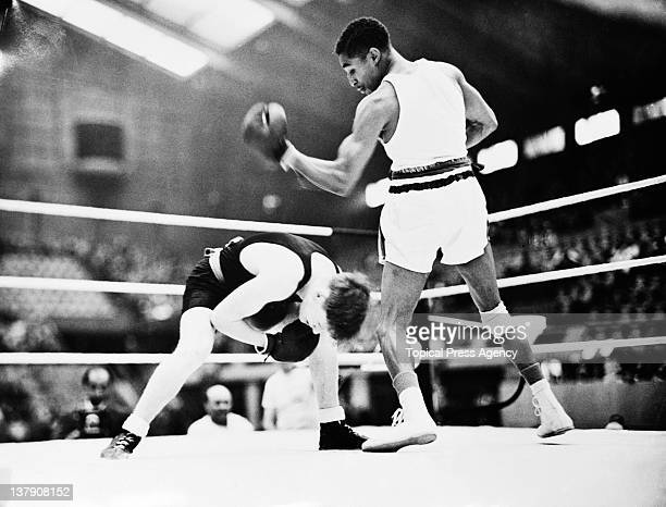 Bob Goslin of New Zealand ducks to avoid a punch from Eddie Johnson of the USA in match four of the featherweight boxing competition at Wembley...