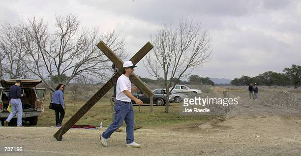 Bob Hanus carries a cross past the entrance to a ranch January 28 2001 where human remains were discovered near Camp Wood Texas The remains may solve...