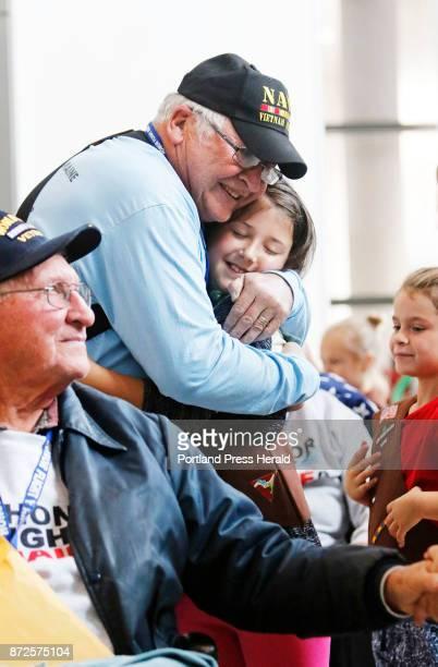 Bob Harris a US Navy veteran gets a big hug from Ava Lemont of Girl Scout Troop 506 in Sabbatus as he and WW II veteran Dale Harris of Hollis arrive...
