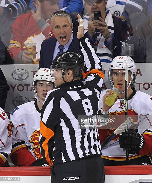 Bob Hartley head coach of the Calgary Flames has words with referee Dave Jackson in third period action in an NHL game against the Winnipeg Jets at...