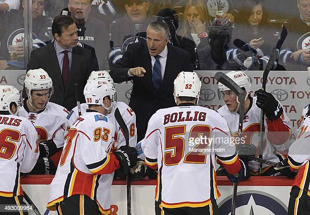 Bob Hartley head coach of the Calgary Flames speaks to his team from the bench in third period action in an NHL game against the Winnipeg Jets at the...
