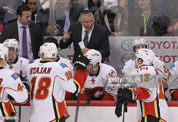 Bob Hartley head coach of the Calgary Flames talks to his team during a break in overtime action in an NHL game against the Winnipeg Jets at the MTS...