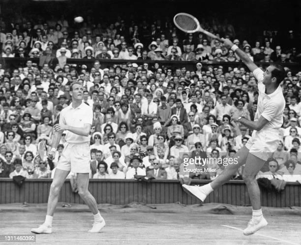 Bob Hewitt of Australia jumps to make an overhead return shot to Boro Jovanovic and Nikola Pilic of Yugoslavia as his compatriot partner Fred Stolle...