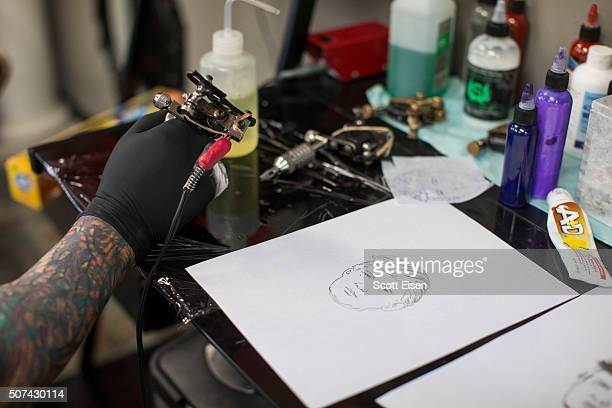 Bob Holmes, owner of the Clay Dragon Tattoo Shop puts more
