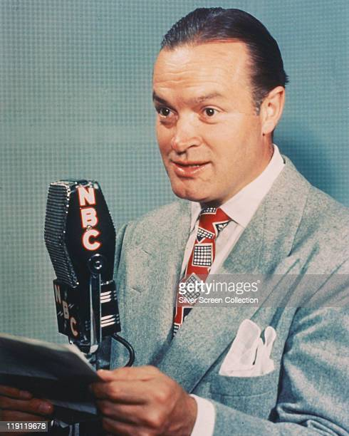 Bob Hope British actor and comedian posing beside an NBC microphone in a studio portrait against a light blue background circa 1950