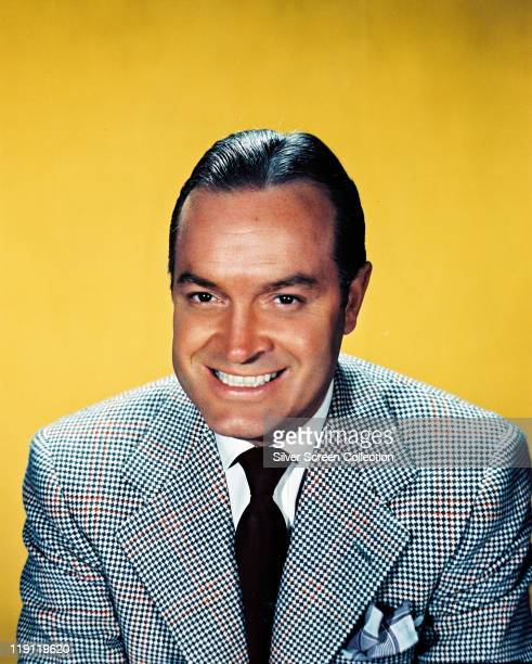 Bob Hope , British actor and comedian, smiling in a studio portrait, against a yellow background, circa 1950.