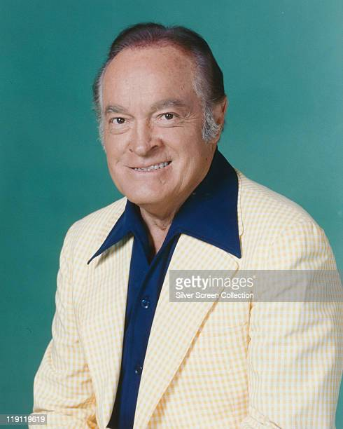 Bob Hope British actor and comedian wearing a white jacket and dark blue shirt in a studio portrait against a petrol blue background circa 1960