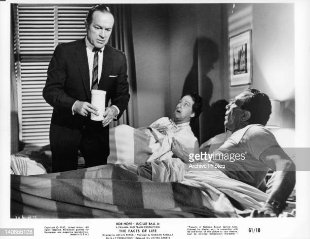 Bob Hope holding canister in between stunned couple in bed in a scene from the film 'The Facts Of Life' 1960