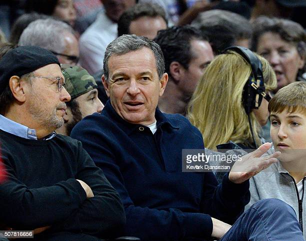 Bob Iger chairman and chief executive officer of The Walt Disney Company talks with actor Billy Crystal during the first half of the basketball game...