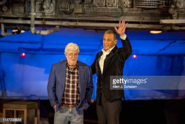 Bob Iger, right, CEO of The Walt Disney Company, waves to the crowd with George Lucas, Star Wars creator, in front of the Millennium Falcon during...