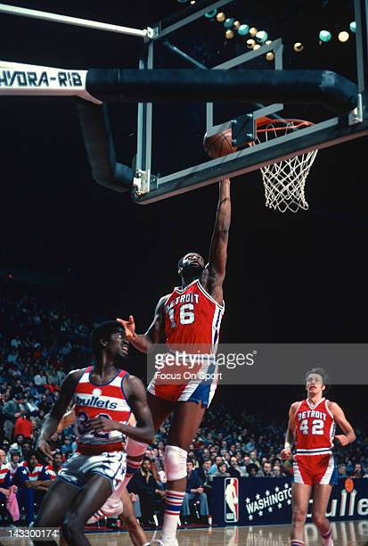 Bob Lanier of the Detroit Pistons lays the ball up over Larry Wright of the Washington Bullets during an NBA basketball game circa 1977 at the...