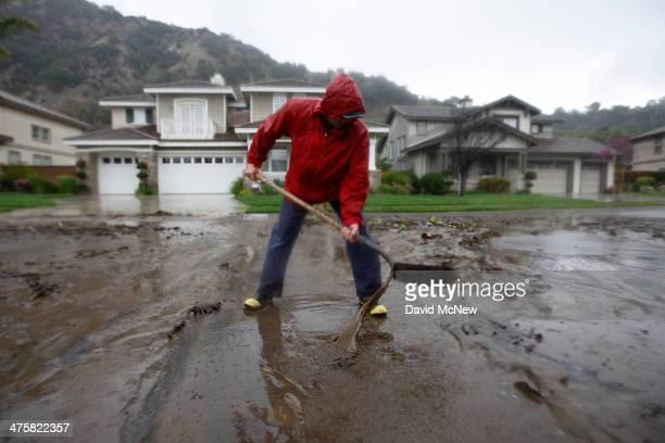 Bob Lavezzari clears ashen mud from his street in a neighborhood threatened with a possible major mudslide below a burned hillside as a storm brings...