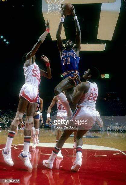 Bob McAdoo of the New York Knicks shoots over Bernard King and Charles Johnson of the New Jersey Nets during an NBA basketball game circa 1978 at the...