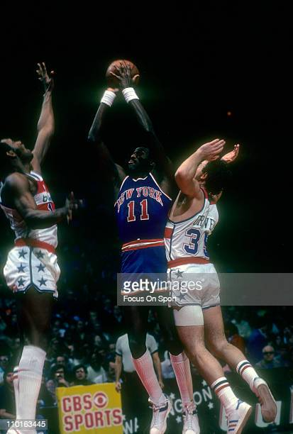 Bob McAdoo of the New York Knicks shoots over Kevin Grevey and Elvin Hayes of the Washington Bullets during an NBA basketball game circa 1978 at the...