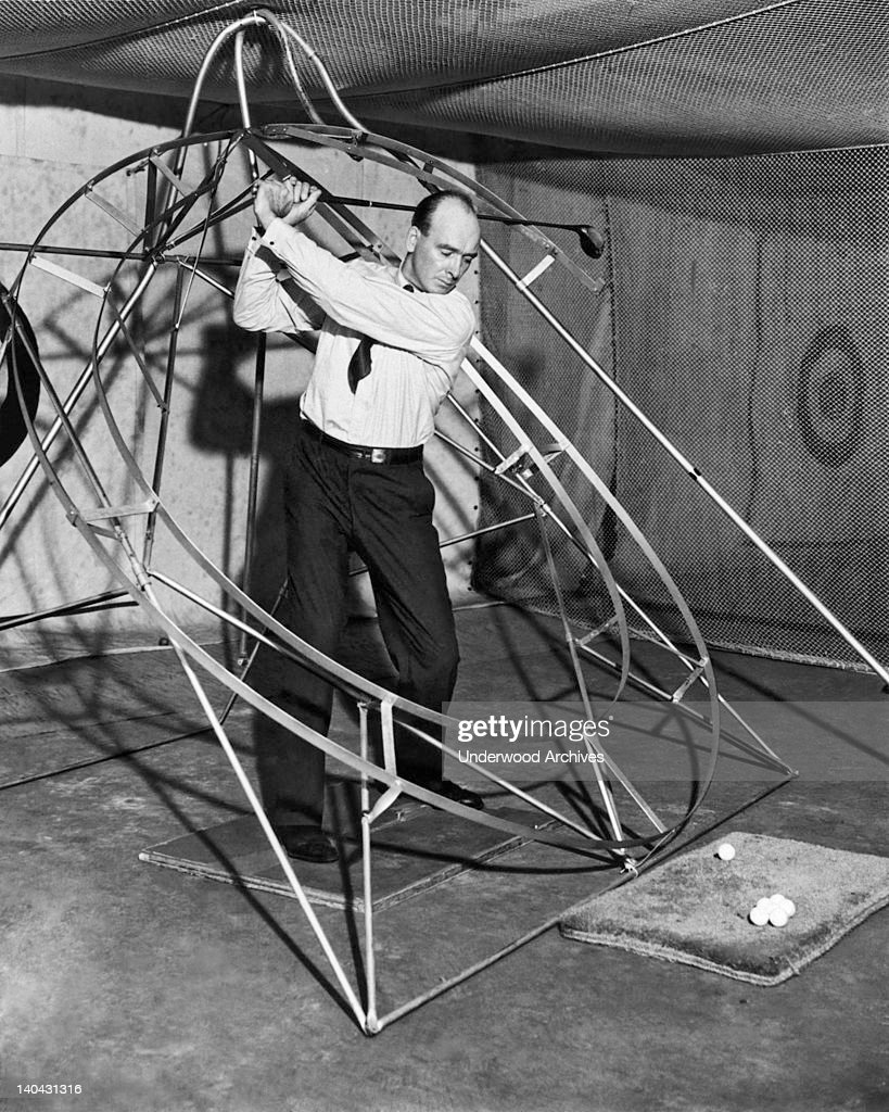 Bob McDonald's perfect golf swing device, Chicago, Illinois circa 1931. The club head rides a groove from back swing to follow through in perfect form.