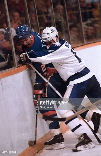 Bob McGill of theToronto Maple Leafs ties up John Tonelli of the New York Islanders March 2 1985 at Maple Leaf Gardens in Toronto Ontario Canada
