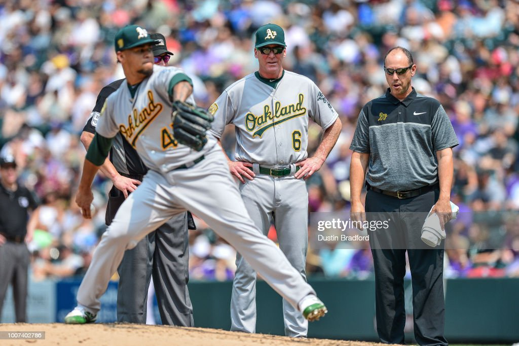 Bob Melvin #6 looks on as Frankie Montas #47 of the Oakland Athletics throws a couple of pitches to assess if he can keep pitching during a game against the Colorado Rockies during interleague play at Coors Field on July 29, 2018 in Denver, Colorado.