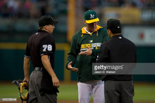 Bob Melvin of the Oakland Athletics argues a call with umpire Alfonso Marquez and umpire Adam Hamari during the third inning against the Houston...