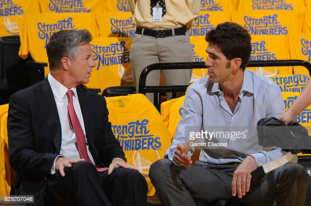 Bob Myers general manager of the Golden State Warriors talks with Neil Olshey general manager of the Portland Trail Blazers in Game Two of the...