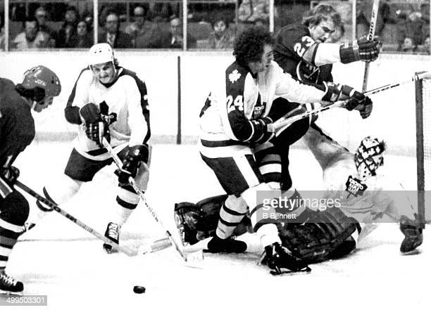 Bob Neely of the Toronto Maple Leafs tries to poke check the puck away from Jude Drouin of the New York Islanders as Brian Glennie and goalie Wayne...