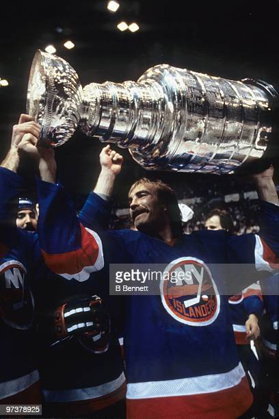 Bob Nystrom of the New York Islanders hoists the Stanley Cup after winning the 1982 Stanley Cup Finals against the Vancouver Canucks at the Pacific...