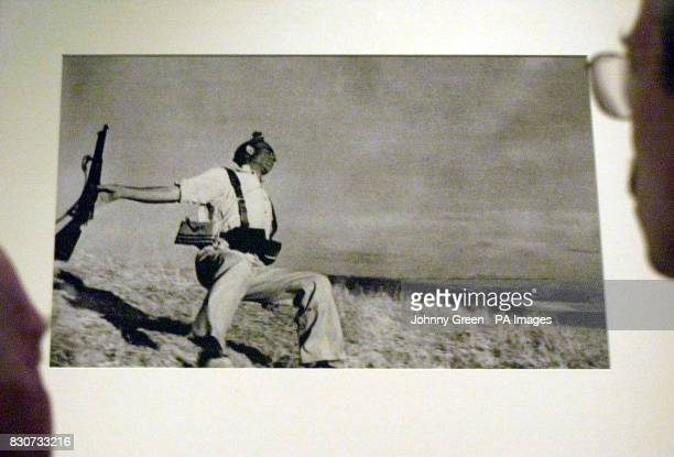 Bob Peters and son Rodney stare at Robert Capa's photograph 'Death of a Militiaman' inside The Imperial War Museum's Spanish Civil War exhibition in...