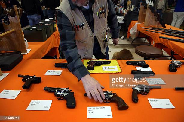 Bob Pfefferkorn sells handguns at his booth at the Gun Knife and Outdoorsmen Show in Fort Wayne Indiana on February 9 2013