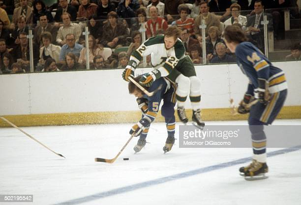 Bob Plager of the St Louis Blues checks Dennis Hextall of the Minnesota North Stars during the 1972 QuarterFinals in April 1972 at the Met Center in...
