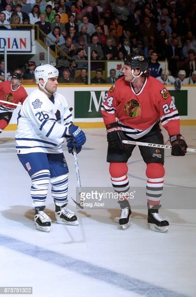 Bob Probert of the Chicago Black Hawks skates against Tie Domi the Toronto Maple Leafs on January 24 1996 at Maple Leaf Gardens in Toronto Ontario...