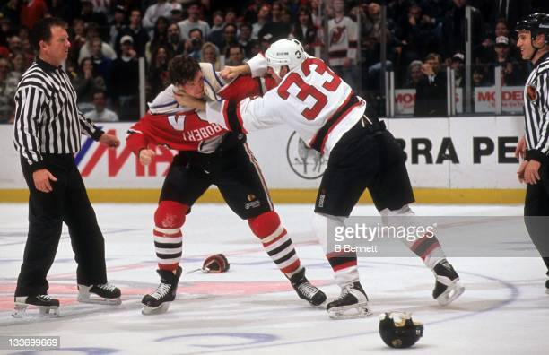 Bob Probert of the Chicago Blackhawks fights with Reid Simpson of the New Jersey Devils circa 1995 at the Continental Airlines Arena in East...