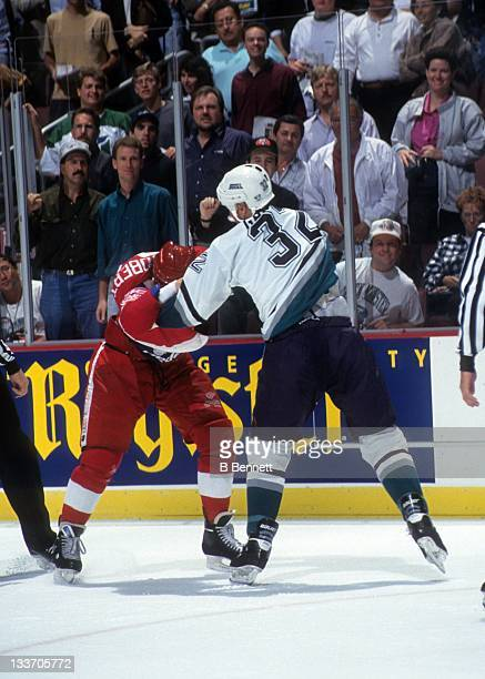 Bob Probert of the Detroit Red Wings fights with Stu Grimson of the Mighty Ducks of Anaheim on October 8 1993 at the Arrowhead Pond of Anaheim in...