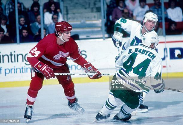 Bob Probert of the Detroit Red Wings is blocked by Dave Babych and Paul Lawless of the Hartford Whalers during an NHL game on December 6 1986 at the...