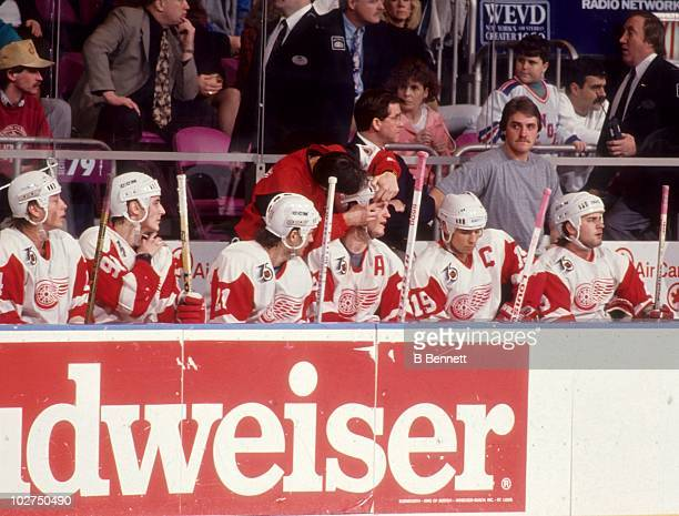 Bob Probert of the Detroit Red Wings receives treatment on the bench as his teammates look on during an NHL game circa 1992 at the Joe Louis Arena in...