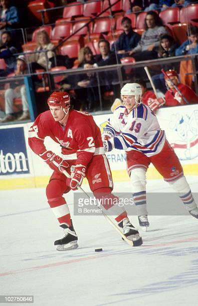 Bob Probert of the Detroit Red Wings skates with the puck as Brian Mullen of the New York Rangers hooks him from behind during an NHL game circa 1991...