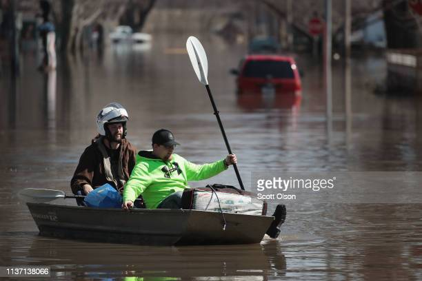 Bob Reafleng recovers items from his flooded home including his motorcycle helmet with the help of Codie Powers on March 20 2019 in Hamburg Iowa...