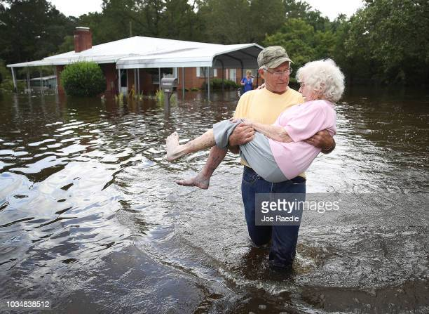 Bob Richling carries Iris Darden as water from the Little River starts to seep into her home on September 17 2018 in Spring Lake North Carolina Flood...