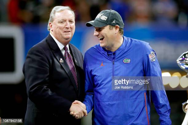 Bob Somers chairman of the Peach Bowl congratulates head coach Dan Mullen of the Florida Gators after his teams win over the Michigan Wolverines...