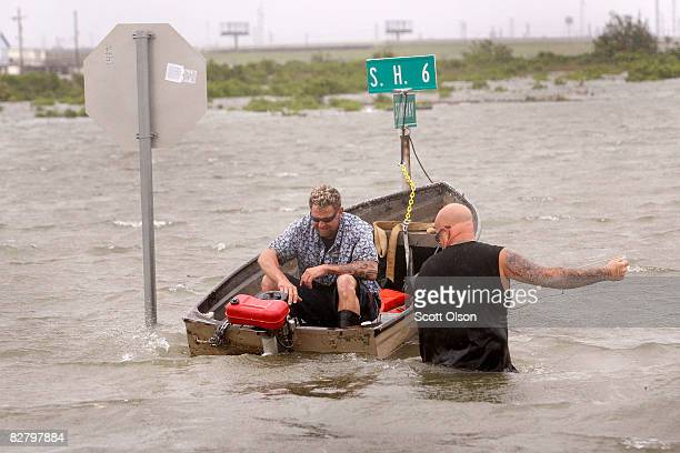 Bob Spillers helps neighbor Jack Horne start a boat so he can return to his home flooded by the tidal surge from Hurricane Ike September 12 2008 in...