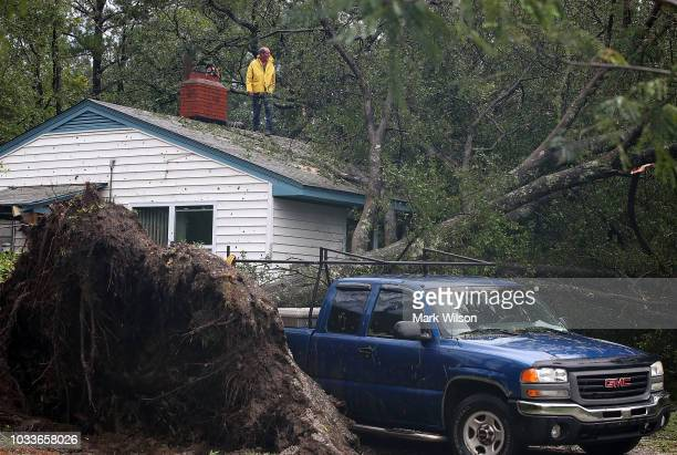 Bob Steigmeyerover starts to cut up a large tree that fell on his house after Hurricane Florence hit the area on September 15 2018 in Wilmington...