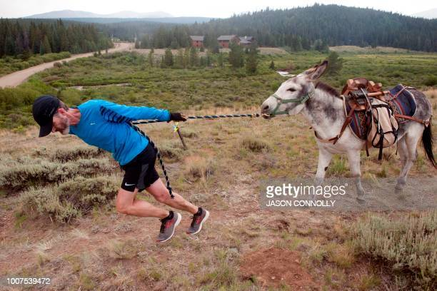 Bob Sweeney of Leadville Colorado pulls his burro Yukon during the 70th Annual Burro Days Race in Fairplay Colorado on July 29 2018 Racers equip...