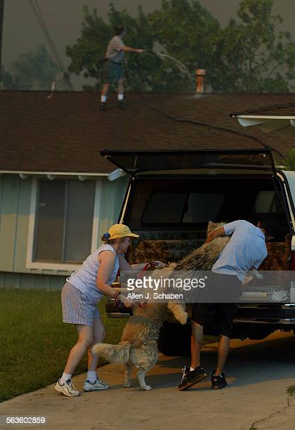 Bob Thibodeau waters down his roof with a garden hose and watches the approaching fire as his wife Diane and son Chris evacuate their dogs as Santa...