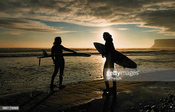 Bob Tweddle and his daughter Emma head out for a morning surf as the sun rises over the North Sea on August 2 2016 in SaltburnByTheSea England After...