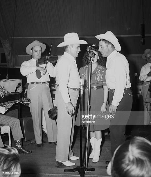 Bob Wills and his Texas Playboys performing at Aragon Ballroom. From left to right: Joe Ferguson, in background with fiddle; Bob Wills, Laura Lee,...