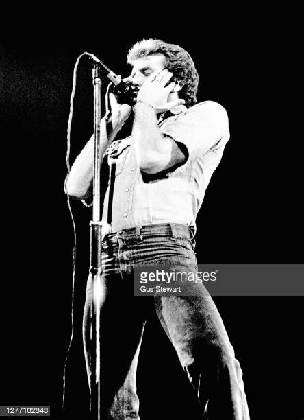Bob Young tour manager and unofficial 5th member of Status Quo plays harmonica on stage at the Hammersmith Odeon London England on 27 February 1976