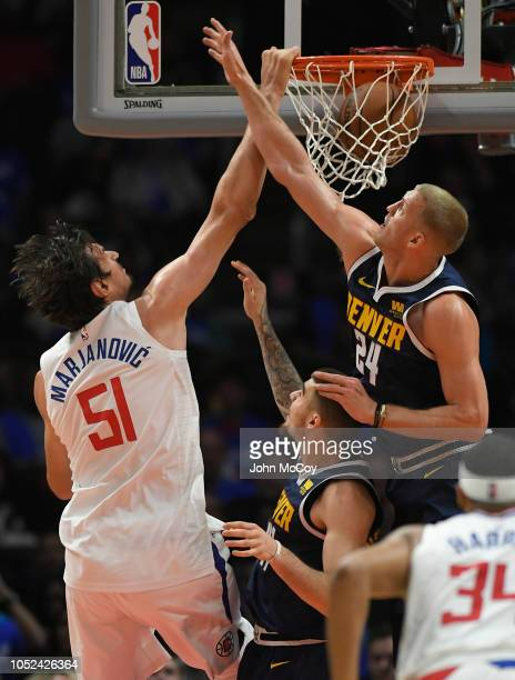 Boban Marjanovic of the LA Clippers dunks the ball over Mason Plumlee of the Denver Nuggets in the second half during the season opening game at...
