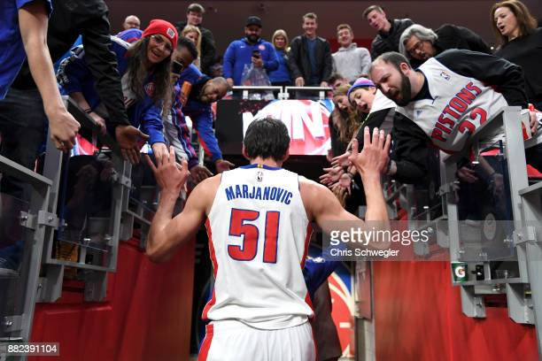 Boban Marjanovic of the Detroit Pistons high five fans after the game against the Phoenix Suns on November 29 2017 at Little Caesars Arena in Detroit...
